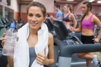 Woman smiling and drinking water in the gym