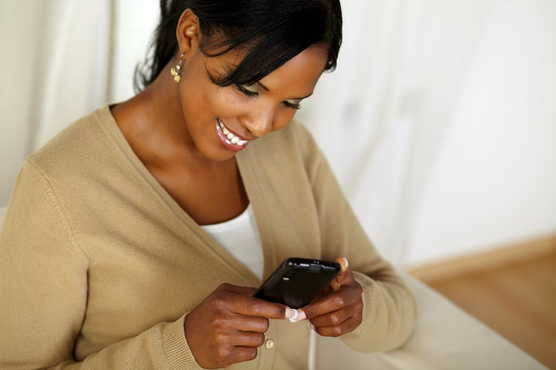 Pretty adult woman reading a message on cellphone
