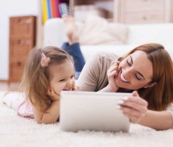 Cute little girl with mom using digital tablet at home