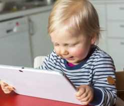 Toddler on a highchair reading a tablet pc; Shutterstock ID 242674822; PO: Brandon for Parents