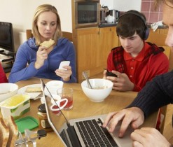 Teenage Family Using Gadgets Whilst Eating Breakfast Together In Kitchen