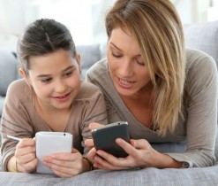 25842161 - mother and daughter playing games with smartphone